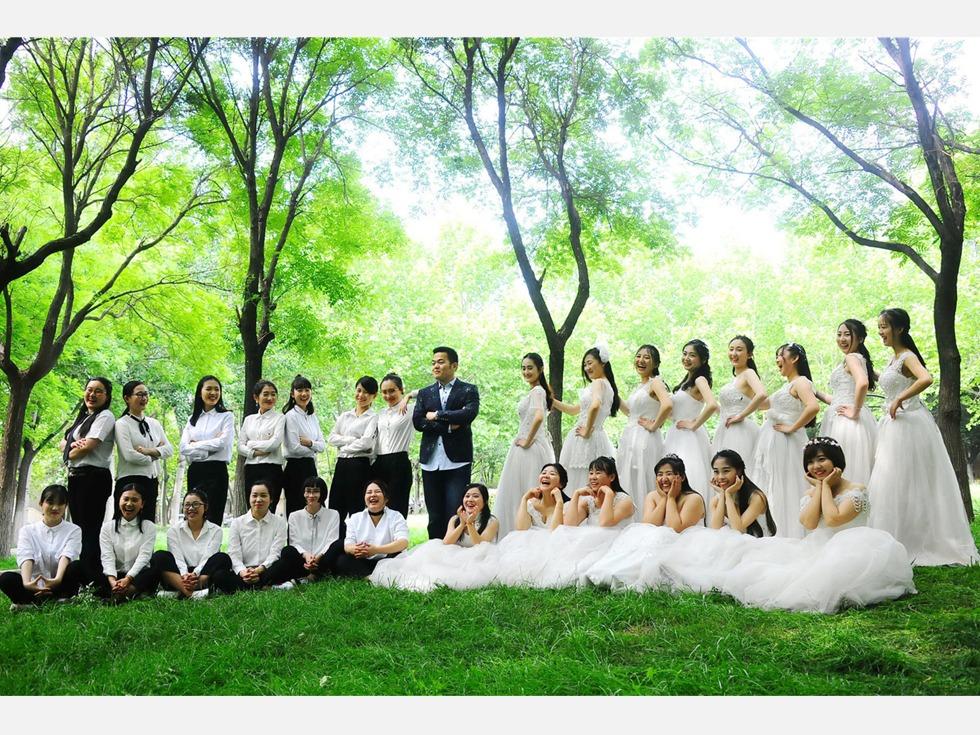 2017年5月15日,济南,在山东财经大学舜耕校区,27位女生穿着婚纱、礼服和班里的唯一一位男生照毕业照。(图源:VCG)